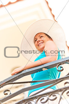 beautiful smiling girl in white hat standing on the balcony