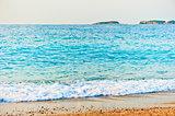 aqua turquoise sea rolls on the beach at dawn