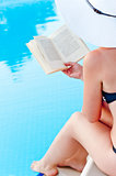 girl sitting near the pool with a book in hand