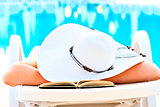 girl asleep in a lounge chair near the pool with a book
