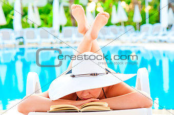 girl in a lounge chair near the pool and reading a romance novel