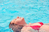girl lying on the water with eyes closed in the pool