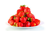 pile of garden strawberry on a plate isolated