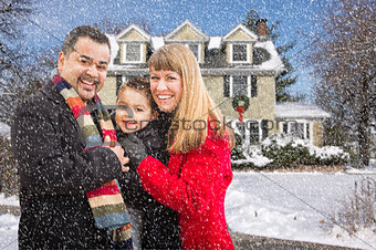 Mixed Race Family in Front of House in The Snow