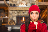 Mixed Race Girl Enjoying Warm Fireplace and Holding Mug