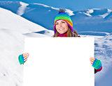Happy girl holding white board, winter outdoor