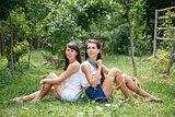 two young females sitting on grass