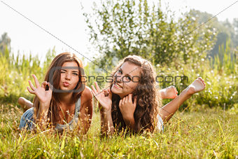 two girlfriends lying down on grass