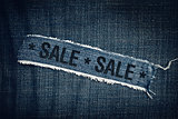 SALE title on torn blue jeans texture