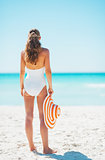 Happy young woman with hat on beach. rear view