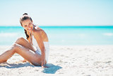 Smiling young woman sitting on beach and looking on copy space