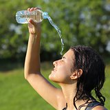 Beautiful woman throwing herself water from a plastic bottle