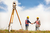 two Surveyor engineers handshaking on the field