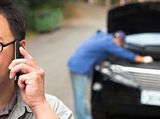 man Talking on Phone While Mechanic Fixes Car