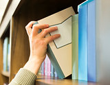 Hand pulling a book off the shelf
