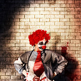 Sinister gothic clown standing on grunge brickwall