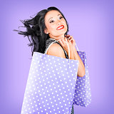 Smiling girl shopper holding purple shopping bags