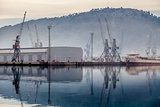 cargo port with cranes in fog with reflection in water.