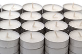 Rows of white wax tea light candles