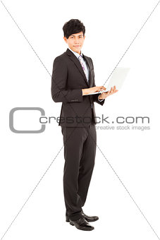 Full length of  young businessman standing with laptop