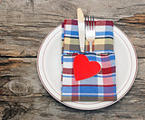 Cutlery in the colorful napkin and red heart on an empty plate