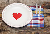 Empty dish, knife and fork and colorful napkin on wood table