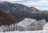 Old wooden cabin in the winter mountains lanscape.