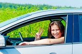 smiling girl driving a car on nature