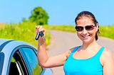 young woman proudly displays the keys to her new car