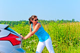 Young beautiful woman is pushing broken car on the road