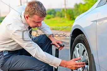 businessman pumps car tire pump
