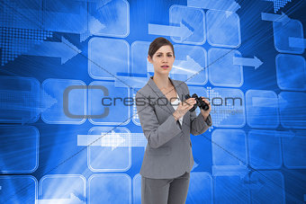 Composite image of curious young businesswoman posing with binoculars
