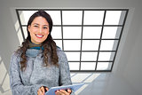Composite image of smiling model wearing winter clothes holding her tablet