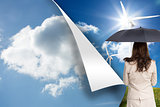 Composite image of rear view of classy businesswoman holding umbrella