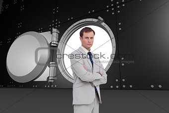 Composite image of serious businessman standing with his arms folded