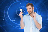 Composite image of charming model holding a bulb in right hand