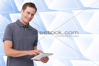 Composite image of smiling young man with tablet computer