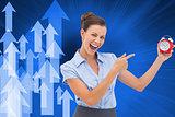 Composite image of businesswoman indicating alarm clock