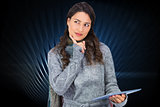 Composite image of pensive model wearing winter clothes holding her tablet