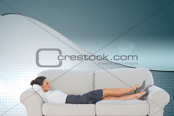 Composite image of smiling business woman lying down on the couch