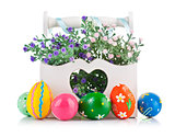 easter eggs in wooden basket with spring flowers