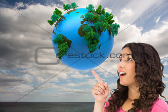 Composite image of surprised brown haired woman pointing out
