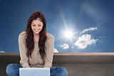 Composite image of brunette sitting on floor using laptop
