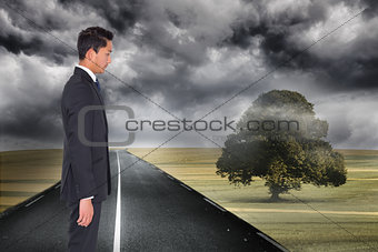 Composite image of frowning businessman looking down