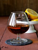 glass of brandy with chocolate on wooden table