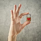 Hand holding padlock with heart shape