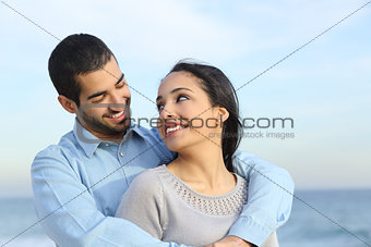 Arab casual couple cuddling happy with love on the beach
