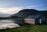 Stone boat shed and mountain reflected in lake at sunrise
