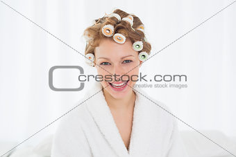 Beautiful woman in bathrobe and hair curlers at home
