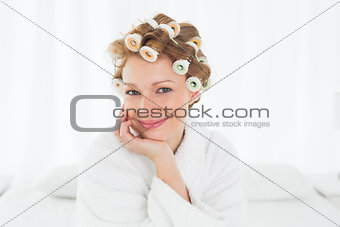 Woman in bathrobe and hair curlers sitting on bed